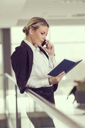 authoritative woman: Modern business woman having a phone conversation with a colleague