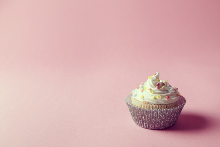 it is isolated: One nicely decorated cupcake with cream and sprinkles on it, isolated on pink background