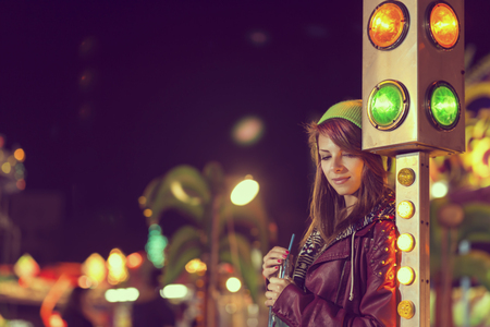 trafficlight: Beautiful young urban girl standing next to a traffic light at an amusement park, drinking energy drink