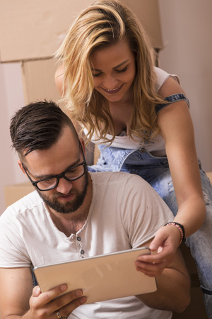 redecorate: Young couple in love moving in a new apartment, sitting on the floor, planning to redecorate their new home Stock Photo