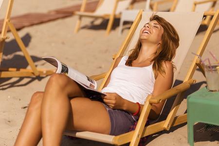 insolación: morena atractiva acostado en una tumbona en la playa, leyendo una revista y disfrutar del sol