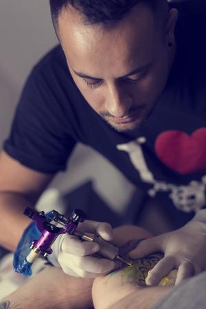 tattoo arm: Male tattoo artist holding a tattoo gun, showing a process of making tattoos on a male tattooed models arm.