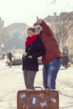 portmanteau: Couple in lovehugging, sightseeing and standing next to a suitcase