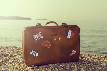 Uitstekende koffer met vlagstickers die op het strand met vreedzame overzees tijdens zonsopgang op Thassos-eiland in Griekenland worden geplaatst