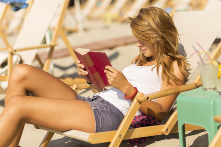 insolaci�n: Attractive brunette lying on a sunbed on a beach and reading a book