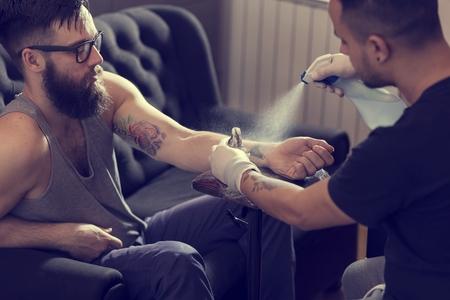 Male tattoo artist holding a tattoo gun, showing a process of making tattoos on a male tattooed model's arm.