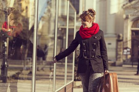 portmanteau: Beautiful, young girl walking by a shop window, carrying a suitcase Stock Photo