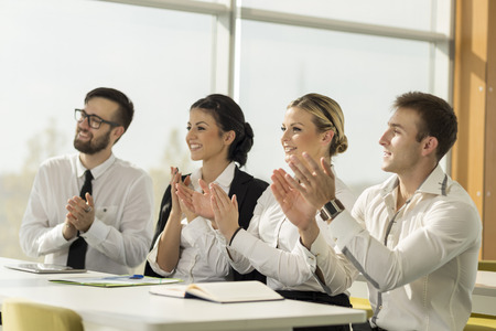 busines: Busines team applauding a colleague on a successful presentation Stock Photo
