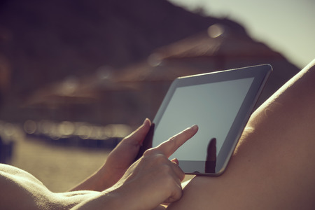 joyfull: Detail of female hand holding a tablet computer and surfing the web while lying on a sunbed on the beach on a summer vacation