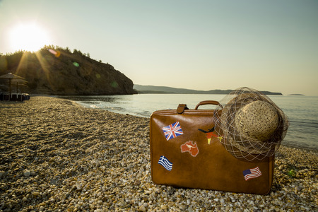 peacefull: Vintage suitcase with flag stickers and a straw hat, placed on the beach with peacefull sea during sunrise on Thassos island in Greece Stock Photo