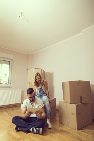 appartment: Young couple in love moving in a new appartment, sitting on the floor, planning to redecorate their new home