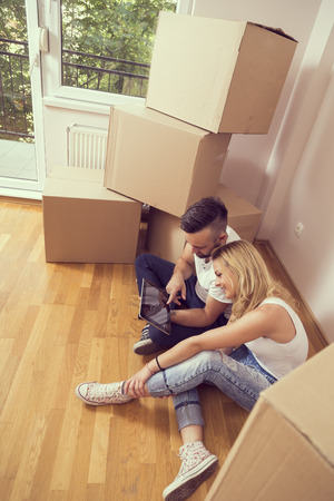 redecorate: Young couple in love moving in a new appartment, sitting on the floor, planning to redecorate their new home