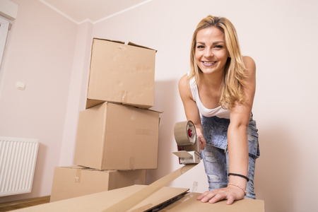 packing tape: Young girl moving in a new apartment,standing surrounded with cardboard boxes, packing and taping boxes Stock Photo
