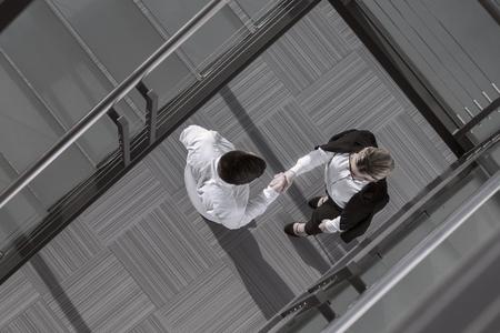 自信を持ってのビジネスマンおよび女性の事務所ビルのロビーで握手の平面図