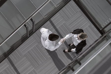 Top view of confident businessman and woman shaking hands in an office building lobby Standard-Bild
