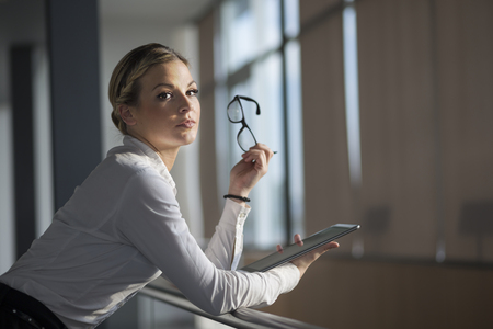 authoritative woman: Strong, confident, business woman standing in an office building hallway, holding tablet computer Stock Photo