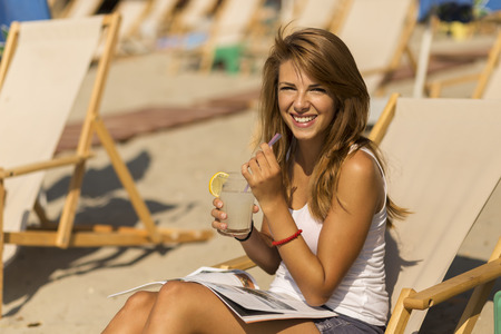 insolaci�n: Attractive brunette lying on a sunbed on a beach, drinking lemonade, reading a magazine and enjoying the sun