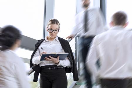 忙しい事務所建物廊下、女性は立っているとメモを取るに焦点を当てるの動きで 3 つのビジネスの人々