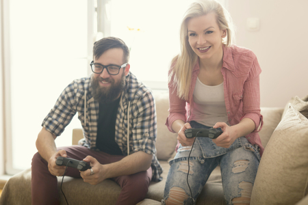 playing video games: Couple in love enjoying their free time, sitting on a couch next to the window, playing video games and having fun. Lens flare effect on the window Stock Photo