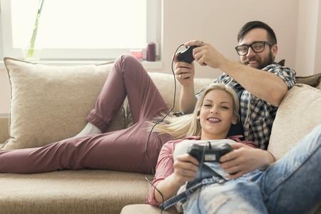 jugando videojuegos: Pareja de enamorados disfrutando de su tiempo libre, sentado en un sof� junto a la ventana, jugar videojuegos y divertirse. efecto de reflejo en la lente en la ventana
