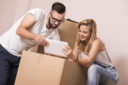 redecorate: Young couple in love moving in a new apartment, standing next to cardboard boxes, holding tablet computer and surfing the web while planning to redecorate their new home