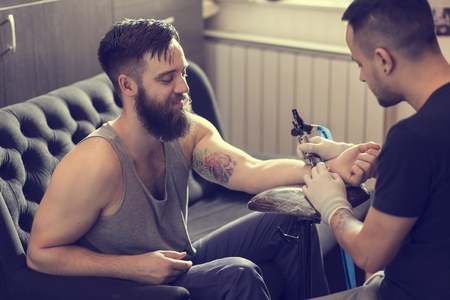 arm of a man: Male tattoo artist holding a tattoo gun, showing a process of making tattoos on a male tattooed models arm.
