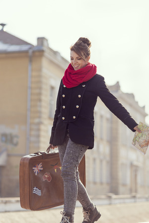 portmanteau: Urban young girl, walking down the street and carrying suitcase Stock Photo