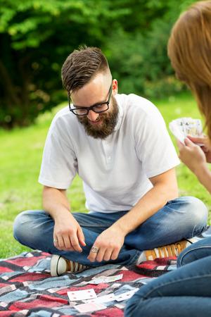 jeu de carte: Couple amoureux sur un pique-nique dans la nature, assis sur un plaid de pique-nique, en jouant un jeu de cartes et avoir du plaisir