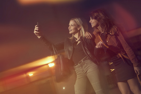 Two beautiful girls taking a night lights selfie on the street before going out to a nightclub Stock Photo