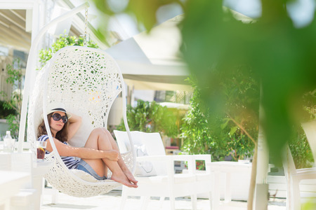 Young woman sitting in a woven rattan hanging basket with cushions, enjoying the morning sun in an outdoor cafe by the sea Stockfoto