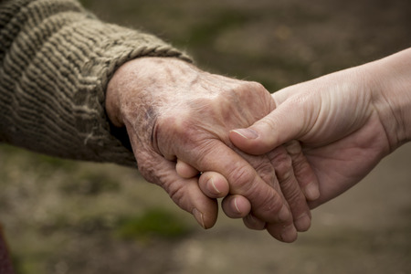 Old and young person holding hands.