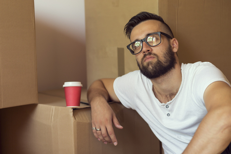 appartment: Young man moving in a new appartment, sitting on the floor, drinking take away coffee, surrounded with cardboard boxes Stock Photo