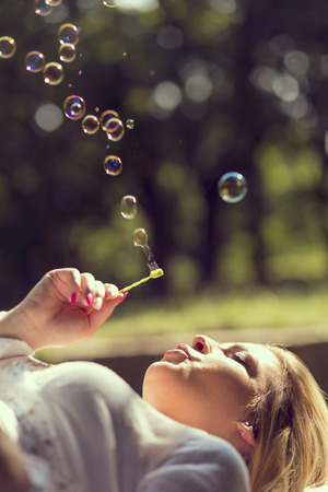 Beautiful young girl lying on a wooden bench in a park, blowing soap bubbles Stock Photo