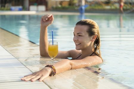 Beautiful blond enjoying on a swimming pool, drinking an orange juice