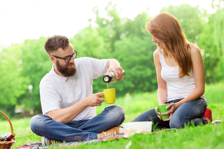 thermos: Young couple on a picnic in a park. Man pouring hot coffee from a thermos bottle