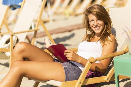 insolación: morena atractiva acostado en una tumbona en la playa y leer un libro