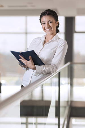 authoritative woman: Strong, confident, business woman standing in an office building hallway, holding a note pad, preparing for a meeting