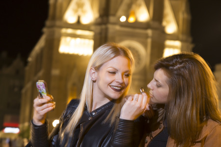 girls night out: Two girl friends on a girls night out, repairing their make up and having fun on the city streets Stock Photo