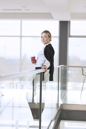 authoritative woman: Young successful business woman standing in an office building hallway, holding a cup of take away coffee