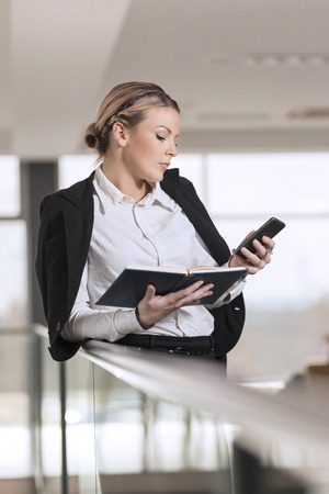 authoritative woman: Modern business woman finishing a phone conversation with a colleague Stock Photo