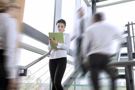 Drukke kantoorgebouw corridor, drie mensen uit het bedrijfsleven in een motie, gericht op de vrouw staan ??en het maken van aantekeningen Stockfoto - 60401416