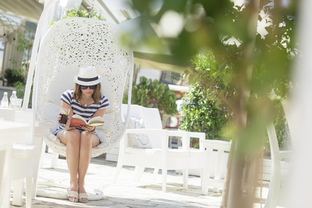 hanging basket: Young woman sitting in a woven rattan hanging basket with cushions, enjoying the morning sun in an outdoor cafe by the sea, reading a book and drinking juice