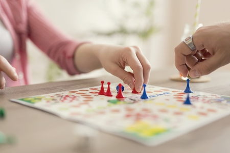 Close up of a couple in love sitting on the floor next to a table, playing ludo board game and enjoying their free time together. Focus on the red figurine Stockfoto