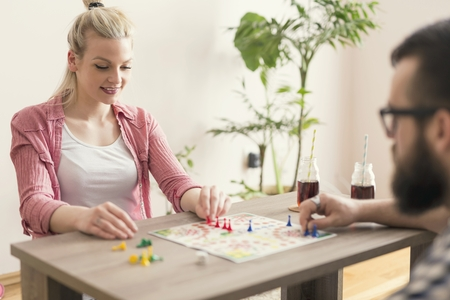 ludo: Couple in love sitting on the floor next to a table, playing ludo board game and enjoying their free time together. Woman repositioning her figurines and winning the game