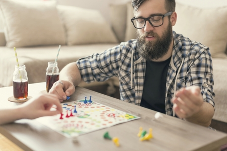ludo: Couple in love sitting on the floor next to a table, playing ludo board game and enjoying their free time together. Man throwing dices for his next move Stock Photo