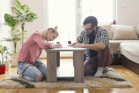 man studying: Young couple in love sitting on the floor next to the table, holding drawing charcoals and sketching on the empty sheets of paper.Leisure time activities,relaxation and spending quality time together Stock Photo