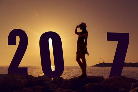 beach happy new year: Happy new 2017 year card. A girl standing on a beach, watching the sunset, standing as a part of 2017 sign Stock Photo