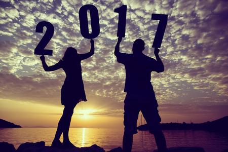 ギリシャ数字 2017 を押し、Syvota 湾の美しい夕日を見て、岩の海岸に立って愛のカップルのシルエット