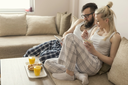 wakening: Couple in love sitting on the couch in the living room, wearing pajamas after getting up in the morning, reading news on a tablet computer and having breakfast