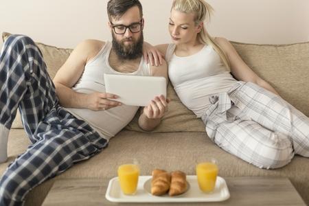 levantandose: Pareja en el amor que se sienta en el sofá de la sala de estar, con un pijama después de levantarse por la mañana, la lectura de noticias en un ordenador tableta y desayunar